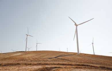 A group of wind turbines on a hill.